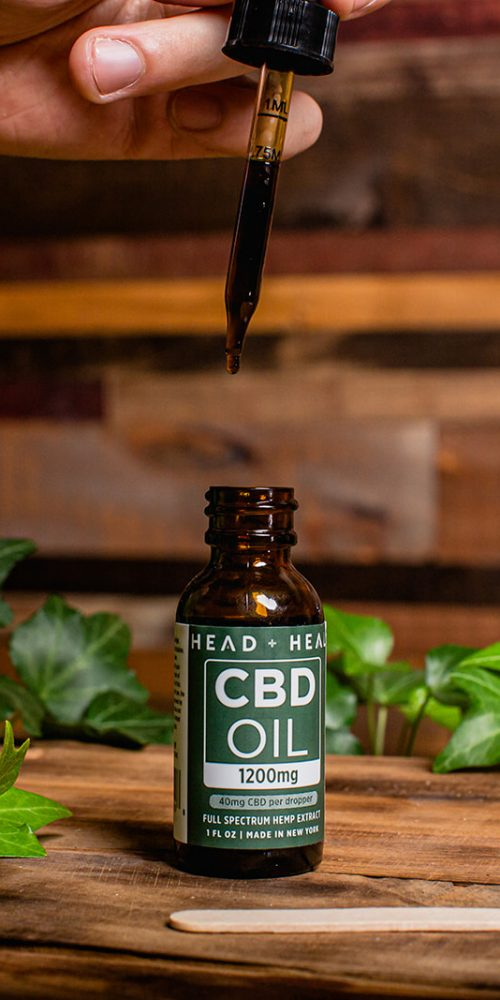 A hand squeezing a dropper of CBD oil into the bottle.