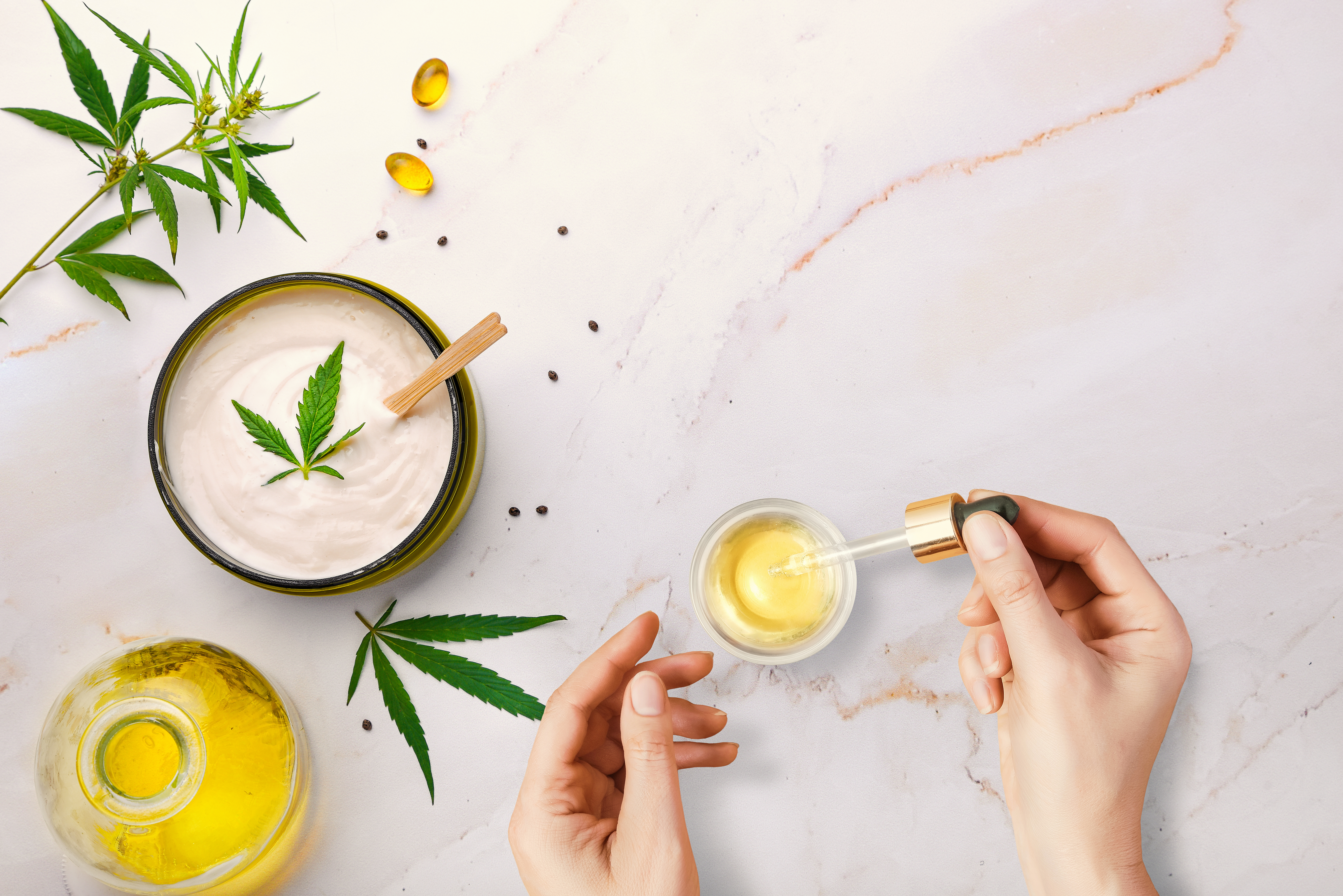 CBd Oil Pipette with CBD cosmetic oil in female hands on a table background with cosmetics, cream with cannabis and hemp leaves, marijuana.
